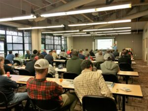 Pesticide school attendees are seated at tables taking notes as Dr. Wayne Buhler teaches.